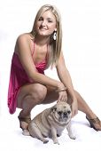 Beautiful young woman with blond hair posing against white background with her pet pug dog. poster