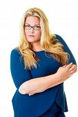 Savvy business woman stares intensely at camera while standing with her arms crossed poster