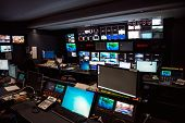 TV Broadcast news studio with many computer screens and control panels for live air broadcast. poster