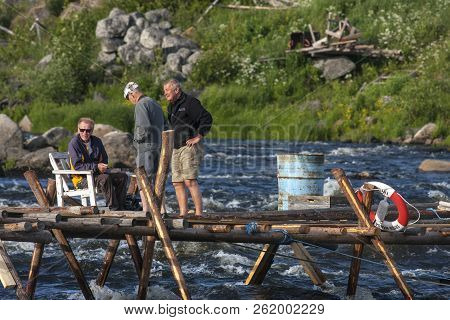 Kukkolaforsen, Sweden On June 27. View Of The Rapids, Pier In The River And Three Unidentified Fishe