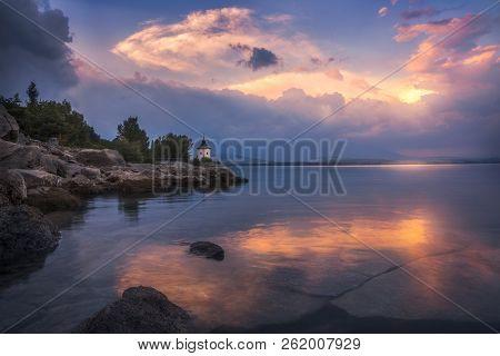 Rocky Beach With Church On Liptovska Mara Lake In Slovakia At Sunset