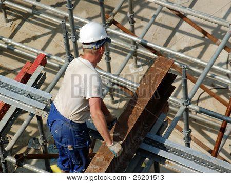 Construction worker detaching steel beam from crane