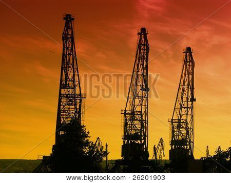 Silhouettes of giant cranes at the port of transhipment against a bloody sunset sky