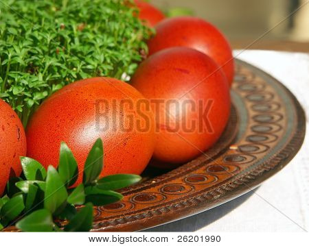 Easter eggs dyed with onion leaf extract arranged on wooden plate with cress