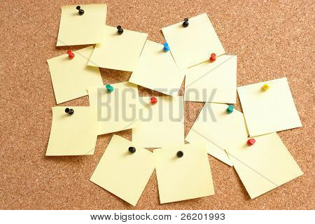Yellow blank post-it notes affixed to the corkboard