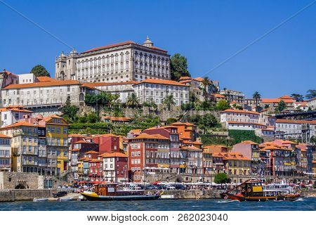 Porto or Oporto, Portugal. Ribeira District with typical colorful buildings, the Douro River and cruise ships for tourists in of Rabelo boats shape