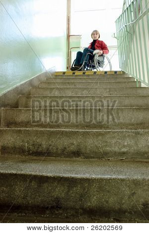 Handicapped woman on wheelchair looking down the stairs in building staircase