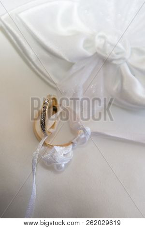 Two Golden Wedding Rings On White Cushion Marriage Celebration Background Concept