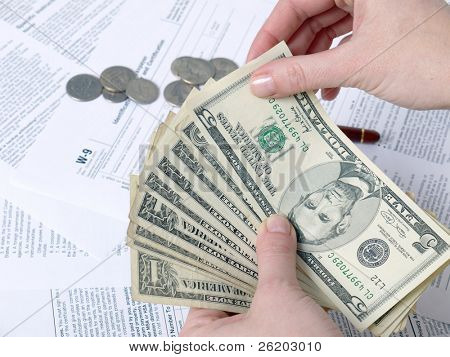 Closeup of female hands counting tax money with W-9 income tax forms underneath