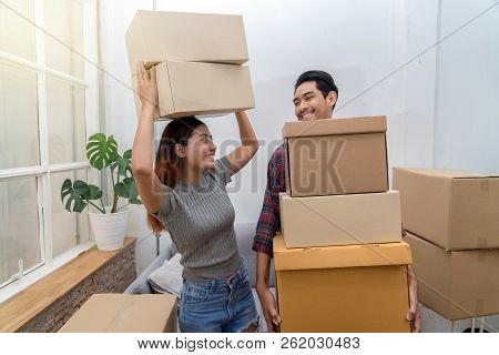 Asian Young Couple Carrying Big Cardboard Box For Moving In New House, Moving And House Hunting Conc