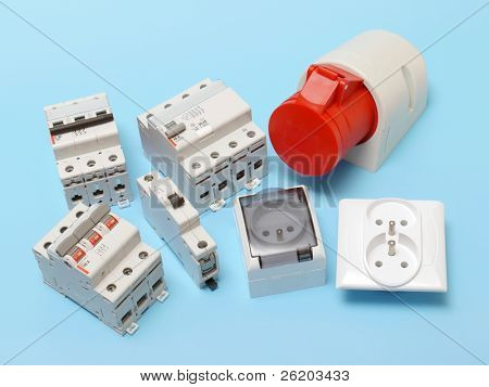 Electrical circuit breakers, main disconnet, power socket and 230 Volt wall sockets shot over blue poster