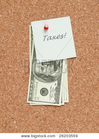 Paper memo note with TAXES word and dollar bills affixed to the corkboard