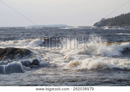 A Lake With Foaming Waves On A Windy Day. Far Rocky Shore, Overgrown With Forest. On The Horizon The