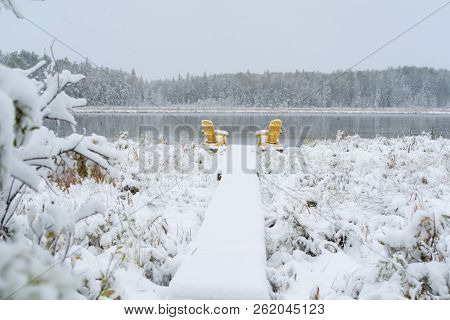 Snow falling on Adirondack chairs on the edge of a lake.