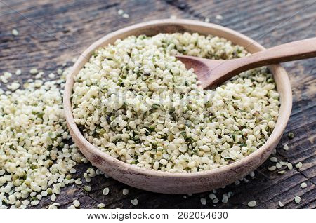 Organic Blanched Hemp Seeds In A Bowl With Spoon On Rustic Wooden Table. Healthy Eating Supplement.