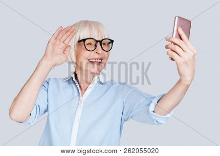 Video Conference. Beautiful Senior Woman Making Video Call And Smiling While Standing Against Grey B