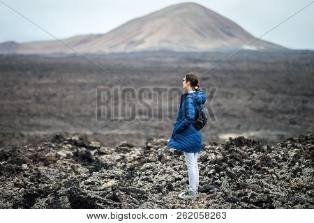 Traveler Woman Enjoy Unique Volcanic Landscapes Of Timanfaya National Park, Lanzarote, Canary Island