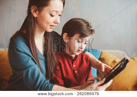 Happy Mother And Toddler Son Using Tablet At Home. Family Playing Computer Or Searching Internet, El