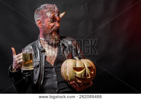 Halloween Holiday Celebration And Party. Man With Satan Horns Hold Pumpkin. Bad Habits And Addiction