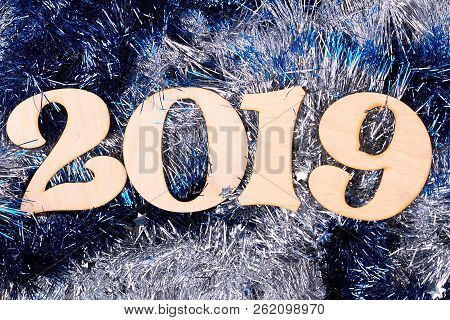 Wooden Number 2019 On Shiny Tinsel Background. Wooden Carved Numbers Forming Number 2019 On Blue And