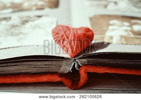 Red Thread Heart On Open Photo Album On Wooden Table Background. Vintage Book Or Photo Album With Th