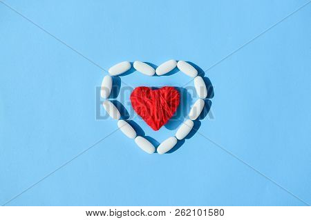 White Pills Capsules And Red Thread Heart Shape On Blue Background. Concept Medical Treatment, Medic