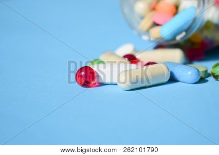 Multicolored Bright Various Type Pills And Capsules Spilling Out Of A Toppled White Pill Bottle. Col