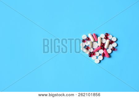 White And Red Various Pills And Capsules In Heart  Shape On Blue Background. Concept Medical Treatme