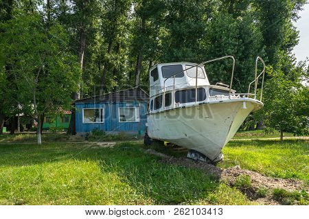 Old Sailing Yacht On Land. Old White Motor Yacht Beached At A Dock For Painting And Repair. Powerboa