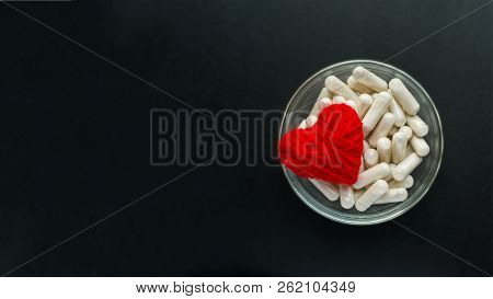 White Capsules, Tablets In Round Plate With Red Thread Heart On Black Background. Blood Pressure, He