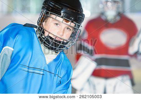 Junior Hockey Player In Blue Uniform And Helmet