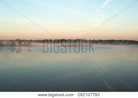 A Small Island On The River Is Covered With Fog. Blue Sky Is Reflected In The Water.