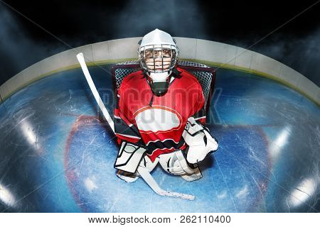 Young Goaltender With Hockey Stick At The Rink