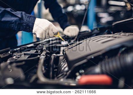 Auto Car Repair Service Center. Mechanic Checking Engine Oil Level