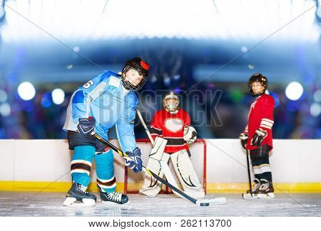 Young Defenseman Passing Puck During Hockey Match