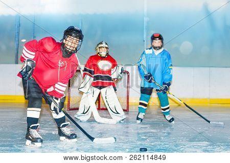 Teenage Boys Playing Hockey On Ice Rink Of Stadium