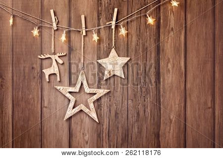 Rustic Christmas Decorations And String Lights Hanging Over A Wood Style Background