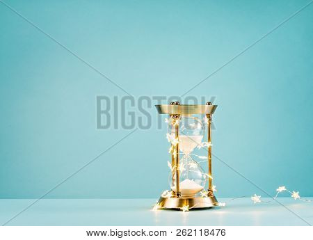 Christmas Or New Years Countdown. Hourglass Wrapped In Lights On A Blue Background.