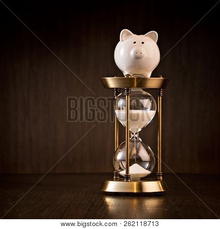 Piggy Bank And Hourglass Over A Dark Wood Background.