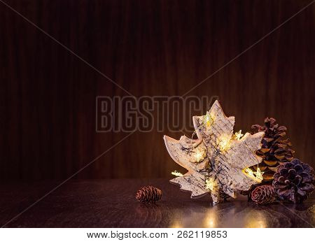 Simple, Natural Christmas Decor Of Pine Cones With Rustic Maple Leaf Ornament Wrapped In Lights On A