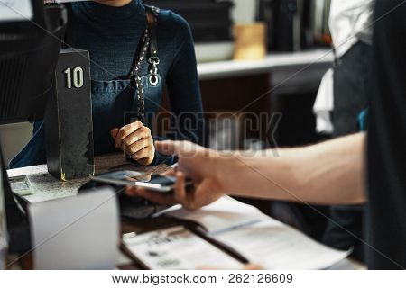 Customer Paying Via Modern Payment Terminal Using Mobile Phone. Nfc Payment.