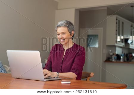 Beautiful senior woman using computer at home, browsing internet. Elderly retired woman using laptop and smiling. Elder lady typing on computer keyboard and surfing the net.