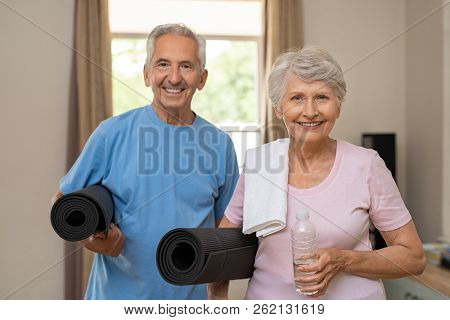 Active healthy senior couple holding yoga mats while going together to training. Happy fitness elderly man and woman looking at camera. Portrait of old couple exercising together at home.