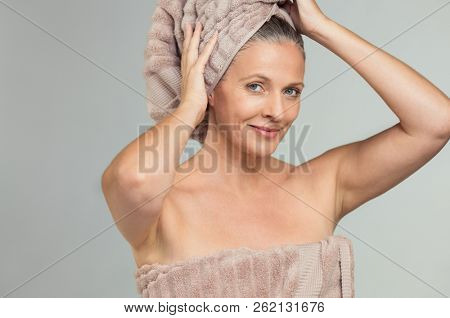 Portrait of beautiful senior woman after shower isolated on grey background. Happy mature woman drying hair after spa sauna bath treatment. Naked lady with wet hair in a towel looking at camera.