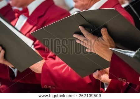 Close Up Of Mens Choir Members Holding Singing Book While Performing In A Cathedral In Rochester, Ke