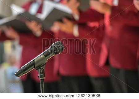 Microphone On A Stand In Front Of Mens Choir Members Holding Singing Book While Performing In A Cath