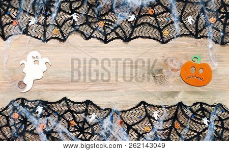 Halloween background. Black cobweb lace border and Halloween decorations on the wooden background with free space for Halloween text, Halloween still life