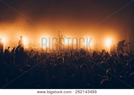Silhouettes Of Concert Crowd In Front Of Bright Stage Lights. A Sold Out Crowd On Rock Concert. Crow