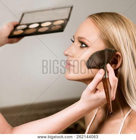 makeup styl?st apply?ng makeup on the model closeup beauty face makeup brushes