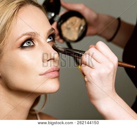 makeup styl?st apply?ng makeup on the model closeup beauty face